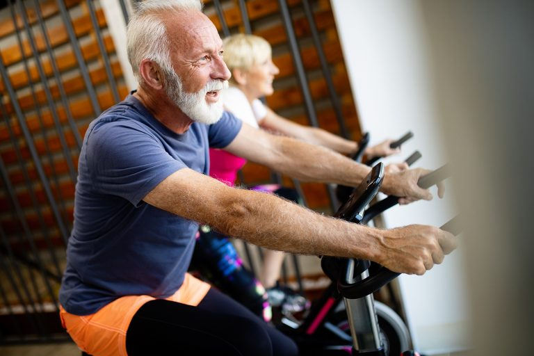 Happy mature people doing indoor biking in a fitness club