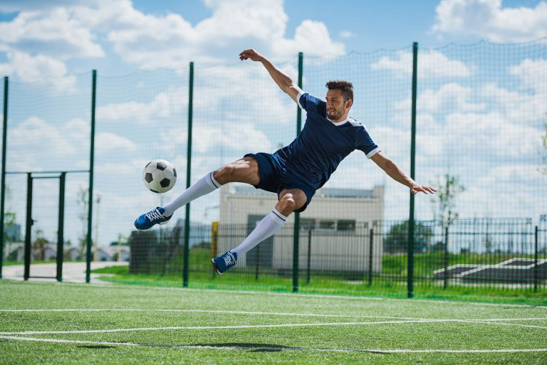 athletic soccer player kicking ball on soccer pitch